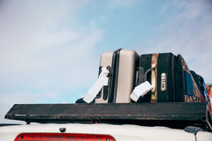 Багажи и сумки аранжировали на крыше автомобиля готовой для отключения в предпосылке неба стоковое фото