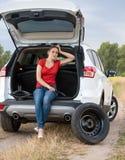 Багажник автомобиля расстроенного усаживания женщины открытый и ждать помощь к chang Стоковые Изображения RF