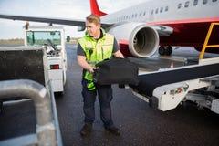 Багаж работника поднимаясь от транспортера прикрепленного к самолету Стоковые Изображения RF