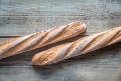 2 багета wholewheat на деревянной предпосылке Стоковые Фотографии RF