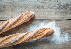 2 багета wholewheat на деревянной предпосылке Стоковые Фото