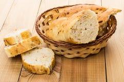 Багет с луками в плетеной корзине и кусках хлеба Стоковые Изображения RF