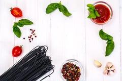 Базилик, красный томат вишни с макаронными изделиями на белой предпосылке Стоковая Фотография RF