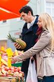 Бакалеи пар покупая на стойке рынка фермеров Стоковые Фото