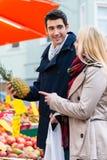 Бакалеи пар покупая на стойке рынка фермеров Стоковое Изображение RF