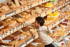 бакалея хлеба мальчика покупая меньший магазин покупкы стоковые изображения