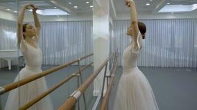 Балерина в белом платье сгабривая ее назад с поднятыми руками во время повторения видеоматериал