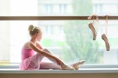 Балерина в розовом платье сидя на окн-силле Стоковые Изображения