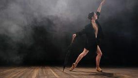 Балерина в черной длинной куртке и сексуальных танцах bodysuit на этапе с волшебными светом и дымом, замедленным движением Молоды акции видеоматериалы