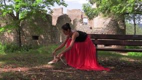 Балерина связывая ботинки pointe сидя снаружи акции видеоматериалы