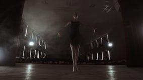 Балерина Prima на pointes тренируя на этапе с фарами в последнем вечере перед важным представлением в опере и видеоматериал