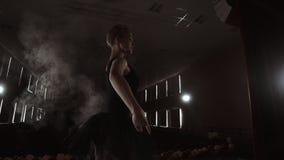 Балерина Prima на pointes тренируя на этапе с фарами в последнем вечере перед важным представлением в опере и сток-видео