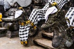 Балийский индусский висок украшенный для традиционного фестиваля Каменные драконы одетые для балийского индусского фестиваля стоковые фото