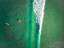 Бали, Индонезия - 12-ое апреля 2018: Вид с воздуха людей занимаясь серфингом на Kuta приставает к берегу, Бали стоковые изображения