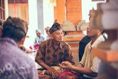 БАЛИ, ИНДОНЕЗИЯ - 13-ОЕ АПРЕЛЯ 2018: Группа в составе карточки балийских людей играя сидя на поле Остров Бали Стоковые Фото