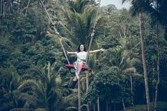 БАЛИ, ИНДОНЕЗИЯ - 26-ОЕ ДЕКАБРЯ 2017: Женщина имея потеху качание в джунглях Женщина отбрасывая в тропическом лесе Бали стоковое фото rf