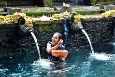 БАЛИ, ИНДОНЕЗИЯ - 18-ОЕ МАЯ Женщина в воде Pura Tirta Empul 18-ое мая 2016 падуба в Бали, Индонезии БАЛИ, ИНДОНЕЗИЯ - 18-ОЕ МАЯ Ж Стоковая Фотография