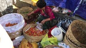 Бали, Индонезия - 21-ое февраля 2019: Женщина продавая овощи на местном органическом рынке видеоматериал