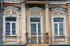 Балкон старого утюга открытый на кирпичной стене с окнами и стеклянной дверью стоковое фото