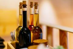 Бальзамический уксус и бутылки оливкового масла на таблице Стоковые Изображения