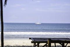 Бамбуковая таблица и стул морем для места для того чтобы увидеть взгляд и яхту в море стоковое изображение rf