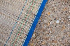 Бамбуковая циновка на песке Стоковые Фотографии RF