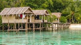 Бамбуковые хаты на деревянных запасах проживания в семье, острове Gam, западном папуасские, радже Ampat, Индонезии Стоковая Фотография