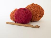 Бамбуковый крюк вязания крючком и яркие шарики шерстей на белой предпосылке Стоковое Фото
