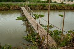 Бамбуковый мост над каналом в саде Стоковые Фото