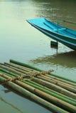 Бамбуковый сплоток и голубая шлюпка на воде Стоковая Фотография