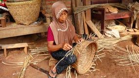 Бамбуковый craftswoman корзины пока делающ его работу стоковое фото rf