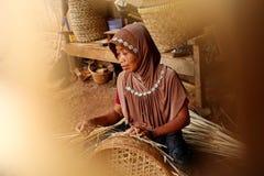Бамбуковый craftswoman корзины пока делающ его работу стоковые фото
