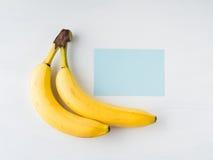 2 банана на белизне с голубой карточкой Стоковая Фотография