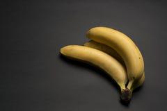 3 банана на темной предпосылке Стоковые Фото