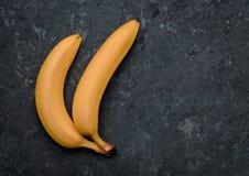 2 банана на черной конкретной таблице fruits тропическо Тенденция минимализма Взгляд сверху стоковая фотография rf
