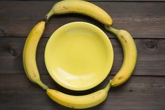 4 банана положенного вокруг желтой плиты Стоковое Фото