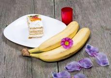 2 банана, плита при торт украшенный с цветками Стоковые Фото