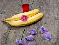 2 бананов украшенного с лепестками сирени и красной свечой Стоковое Фото