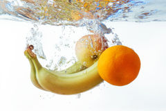 Бананы и апельсины яблоко упали в воду Стоковая Фотография