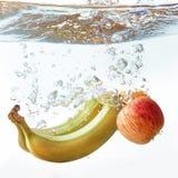 Бананы и апельсины яблоко упали в воду Стоковые Фото