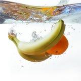 Бананы и апельсин упали в воду, изолированную на белизне Стоковые Фото