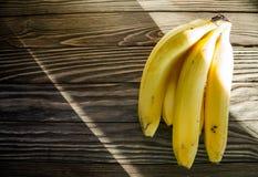 Бананы на деревянной предпосылке в лучах солнечного света Стоковое Фото