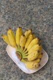 Бананы устанавливают на розовой плите на цементе Стоковая Фотография RF
