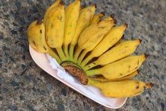 Бананы устанавливают на розовой плите на цементе Стоковая Фотография