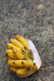 Бананы устанавливают на розовой плите на цементе Стоковые Изображения RF