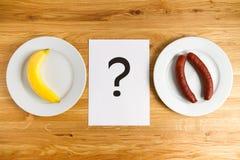 Банан или сосиска, здоровье или рак, плодоовощ или мясо Стоковая Фотография RF