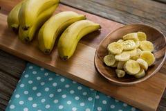 Банан и куски банана в плите держали на прерывая доске Стоковое фото RF