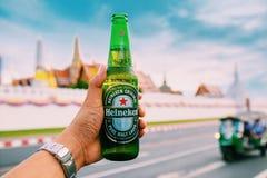 Бангкок, Таиланд - июнь 2019: врученная бутылка холодного пива heineken на тайском дворце виска стоковая фотография
