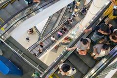 БАНГКОК, ТАИЛАНД - 26-ОЕ АВГУСТА: Множественные покупатели переходов эскалаторов от одного пола к другим в торговом центре термин стоковые изображения rf