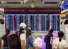 БАНГКОК, ТАИЛАНД - 26-ОЕ АВГУСТА: Путешественники смотрят расписание расписания полетов на международном аэропорте Suvarnabhumi в стоковая фотография rf